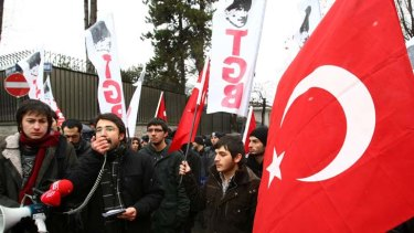 Turkish students hold Turkish flags as they stage a protest outside the French Embassy in Ankara.