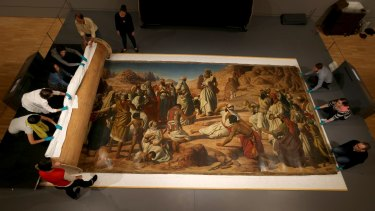 Conservators and volunteers carefully roll out a large-scale John Herbert painting at the National Gallery of Victoria.