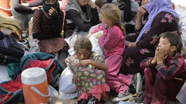 Displaced people from the minority Yazidi sect, fleeing the violence in the Iraqi town of Sinjar, rest at the Iraqi-Syrian border crossing.