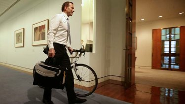 Prime Minister-elect Tony Abbott wheels his bicycle from his old office to his Prime Ministerial office, at Parliament House in Canberra on Monday.