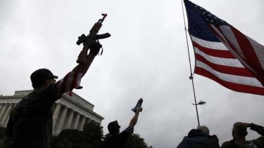 Gun culture runs deep in the US. A group of about twenty demonstrators raise their toy guns at a passing helicopter near the Lincoln Memorial as they march in a 'Toy Gun March' demonstration, organized by a Libertarian website to highlight Second Amendment gun right