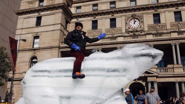 Sculptor Mark Coreth rides his life size ice polar bear in Circular Quay in central Sydney.