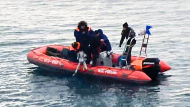 Rescue workers lift a fragment of the plane from waters outside Sochi.