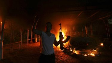 An armed man outside the burning US Consulate in Benghazi.