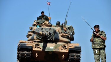 An officer directs operations as Turkish tanks deploy on the Syrian border.