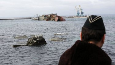 A Ukrainian navy sailor looks at the scuttled Russian ship from the Black Sea shore.