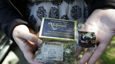 "A customer who identified herself as ""Tracy"" displays dried marijuana, a pot-infused chocolate bar and a marijuana truffle that she bought in Seattle."