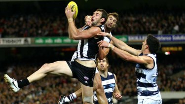 Travis Cloke of the Magpies marks under pressure from Corey Enright.
