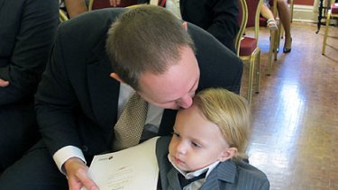 New minister Curtis Pitt kisses son Tristan ahead of his swearing-in.