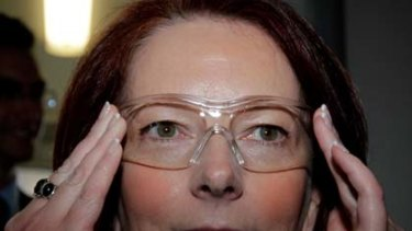 Julia Gillard puts on safety glasses attending a workshop today in Perth.