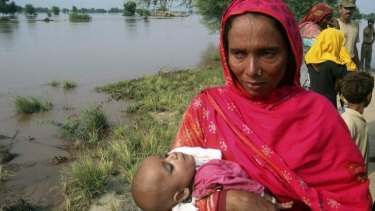 A mother carrying a child cries while evacuating her home along the flooded Chenab River, in Jhang, Pakistan.