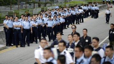 Powerless: Police officers gather as protesters block the entrance to Hong Kong's chief executive's offices.