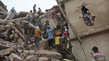 Bangladeshi rescue workers search for victims Friday, April 26, 2013 amid the rubble of a building that collapsed Wednesday in Savar, near Dhaka, Bangladesh.