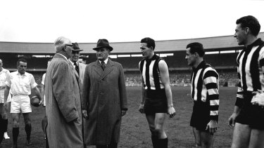 Collingwood players Murray Weideman and Thorold Merret meet Sir William Slim at the 1958 VFL grand final.