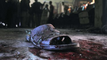 Ruthless ... A blood-stained shoe of a victim lies on the ground at the site of a grenade attack on a crowded cinema that killed 13 and wounded many others in Peshawar, Pakistan.