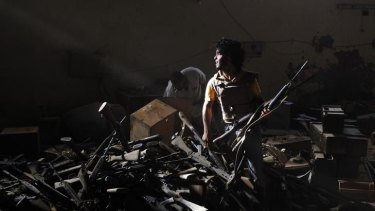 An anti-Gaddafi fighter at a pro-Gaddafi weapons and ammunition compound in a village near Sirte.