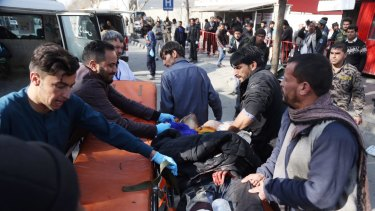 An injured man is moved to a stretcher outside a hospital following the ambulance explosion.