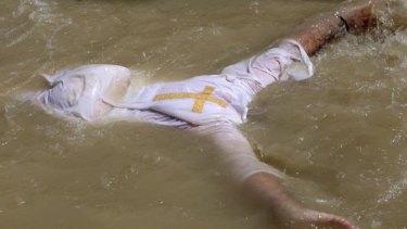 An Orthodox Christian pilgrim immerses himself in the Jordan River.