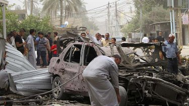 Residents inspect the site of a bomb attack in the town of Taji, about 20 km north of Baghdad.