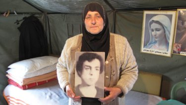 Majida Bashasha, with a photo of her missing brother Ahmad, in the tent she lives in outside the United Nations offices in Beirut.