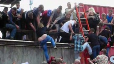 People try to escape over a wall  after a panic at Loveparade 2010 in Duisburg, Germany.