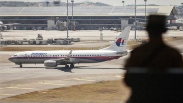 A man looks on as an aircraft operated by Malaysian Airline taxis on the tarmac at Kuala Lumpur International Airport.