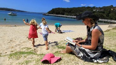 Still at the office ... businesswoman Cassandra Kelly, the joint chief executive of Pottinger, reads a book for work while her children enjoy Clifton Gardens beach in Mosman.