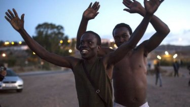 Free: Migrants celebrate after scaling the fence that divides Morocco and the Spanish enclave of Melilla.