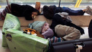 Stranded passengers rest as they wait for a flight at Barajas Airport, in Madrid, Spain.
