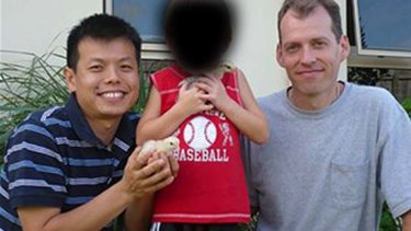Peter Truong (left) and Mark Newton (right) with their son outside their home in Cairns.