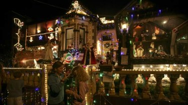 Deck the streets ... children enjoy the Christmas lights at a house on Frazer Street, Dulwich Hill. The owner, Michael Bonifacio, says he spends six weeks preparing the display.