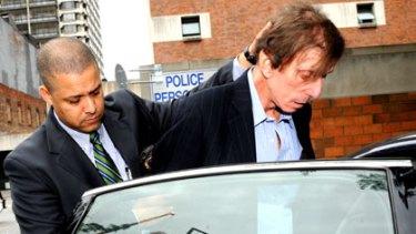 Oscar-winning songwriter Joseph Brooks is led away by police.