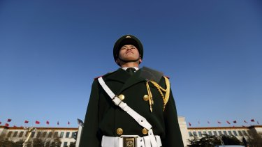 A paramilitary police officer stands outside the Great Hall of the People in Beijing, China.