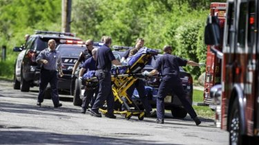 Rescue workers take a stabbing victim to an ambulance in Waukesha, Wisconsin.