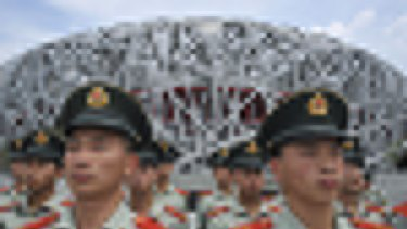Paramilitary policemen in front of the main Olympic stadium are part of a clampdown as Beijing gets ready to welcome the world.