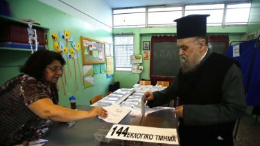 More than one nation's fate in his hands ... a Greek Orthodox priest casts his vote in an Athens primary school yesterday.