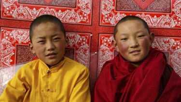 Two young nuns relaxing outside the main temple in the afternoon. Their life of devotion starts when girls are as young as six.