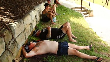 Cooling off ... tourists seek comfort in a patch of shade at Sydney's Bondi Beach.