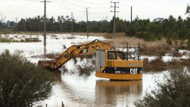 Excavation equipment near Monash Freeway well on its way to complete submersion.