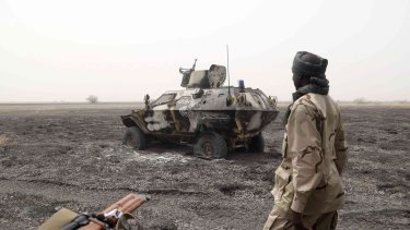 A file photo of a Chadian soldier walking past an armored vehicle that the Chadian military said belonged to Boko Haram.