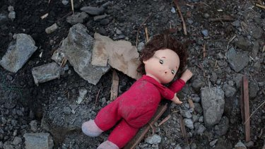 Left behind... a child's doll in the rubble of the town.