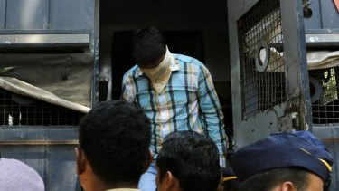 One of the men convicted of gang raping a photojournalist exits a police van as he is brought to prison.