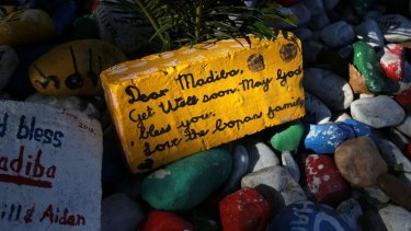 Warm wishes: A get-well message is seen on a brick outside Nelson Mandela's garden in Houghton, Johannesburg on Saturday.