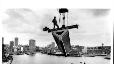 A roof section is lifted over Circular Quay during the  Sydney Opera House construction in 1967.