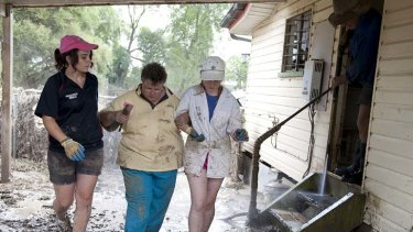 Trying time … volunteers help Patricia Budd as she returns to her home in Mitchell, about 500 kilometres west of Brisbane, to survey flood damage.
