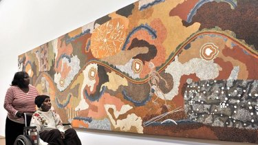 Daisy Leura Nakamarra views the work of her late husband Tim Leura Tjapaltjarri.