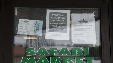 Signs on the door of Safari Market, a Somali-owned coffee shop and grocer that caters to the local Muslim community, advertise services for immigrants.