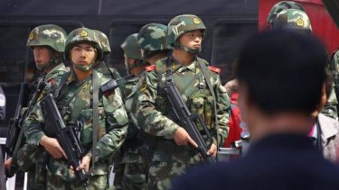 Paramilitary policemen stand guard near the exit of Urumqi's South Railway Station, scene of  a bomb and knife attack on Wednesday.