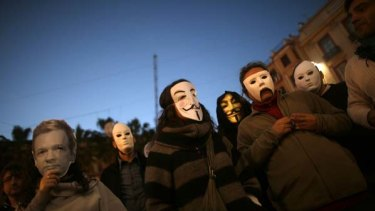 """WikiLeaks supporters wear masks of the """"Anonymous"""" internet activists and an Assange mask, left, at a rally in Malaga, Spain."""