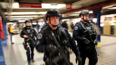 Police officers patrol in the passageway connecting New York City's Port Authority bus terminal and the Times Square subway station.